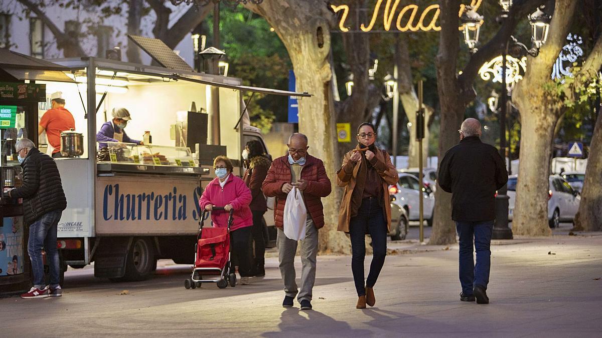 Transeúntes en el paseo de la Alameda Jaume I de Xàtiva ante una parada de churros, en una imagen de esta semana   PERALES IBORRA
