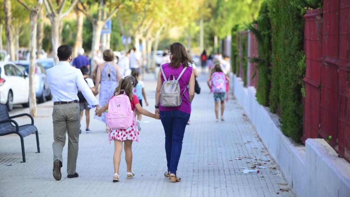 Un hombre  y una mujer acompañan a una menor al colegio en Cartagena.