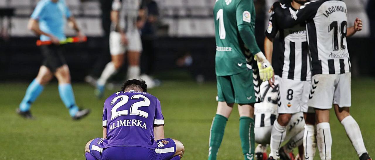 Pablo Pérez, abatido al final del partido, mientras los jugadores del Catellón celebran la victoria.