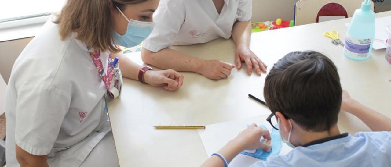 Personal sanitario haciendo actividades con un menor.  | INFORMACIÓN