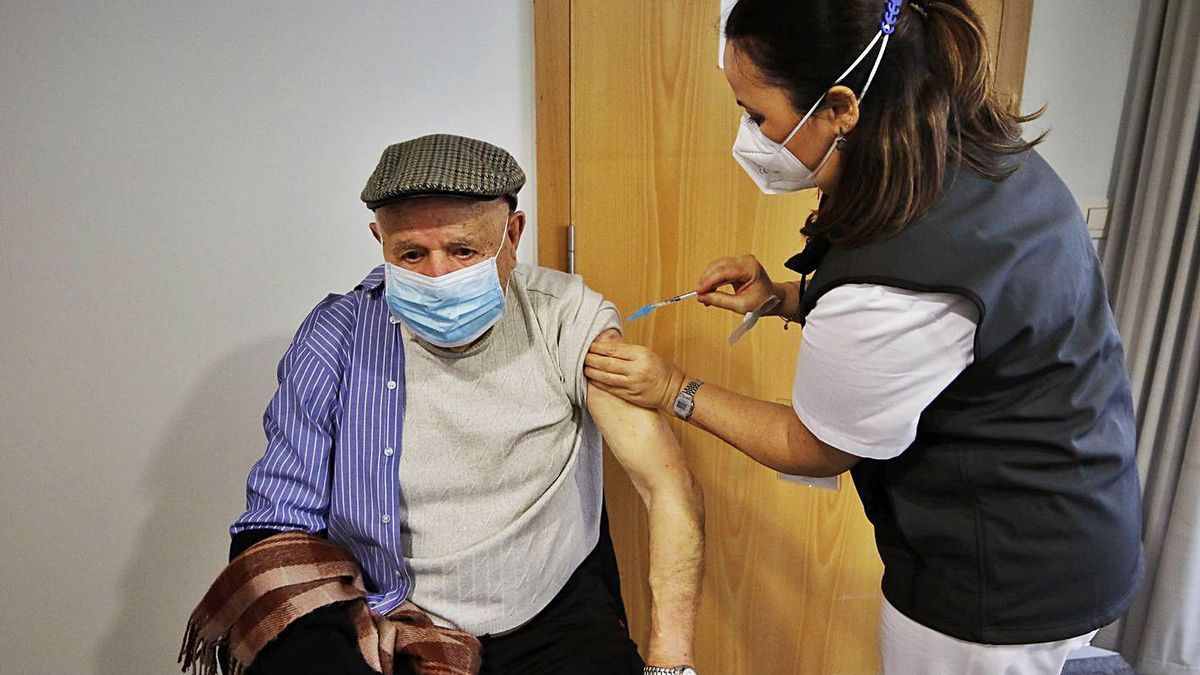 Una sanitaria vacuna a un mayor contra el coronavirus en Vigo. |   // ALBA VILLAR