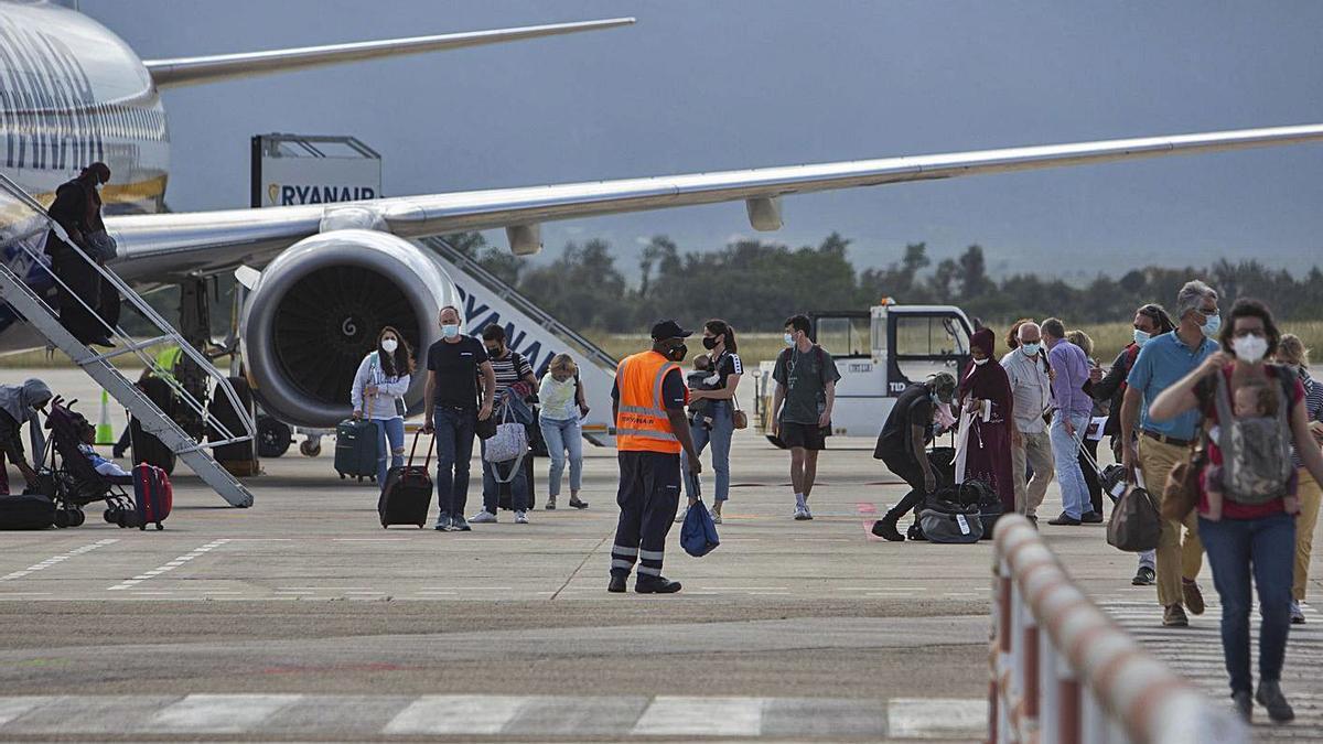 Turistes baixen d'un avió de Ryanair a Girona, aquest mes de juny.  | DAVID APARICIO