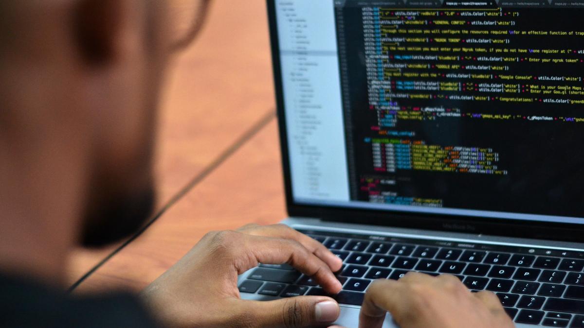 Un hombre teclea en un ordenador.