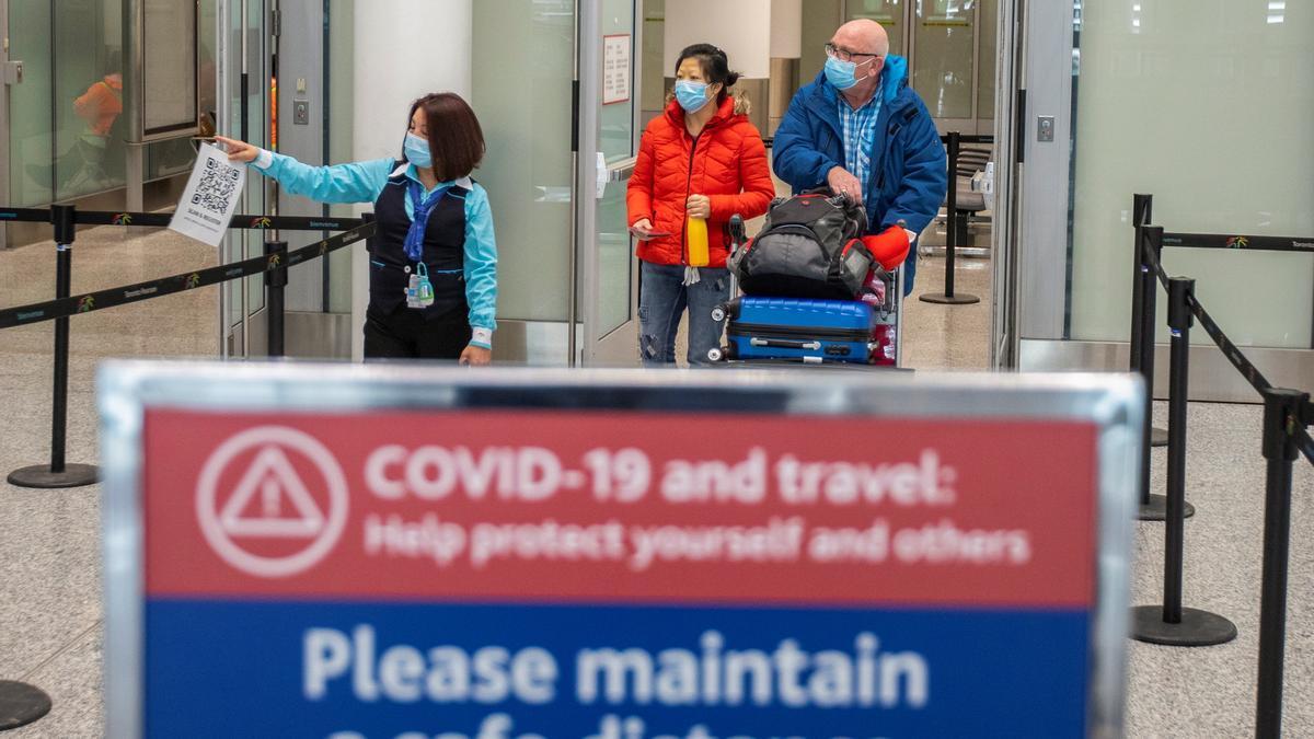 Pasajeros pasan frente a una señal de advertencia del Covid en el aeropuerto de Toronto