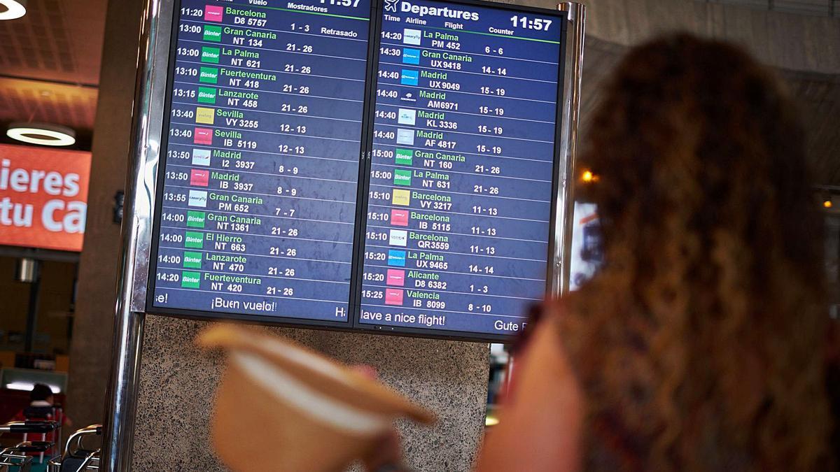 Una mujer mira el panel de información de vuelos nacionales e interislas en el aeropuerto de Tenerife Norte-Los Rodeos.