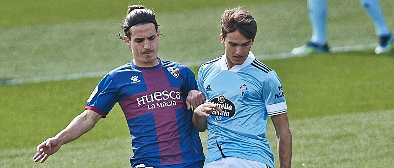 Denis Suárez disputa un balón a Jaime Seoane durante el encuentro de Liga disputado ayer contra el Huesca en el Alcoraz. |  // LOF