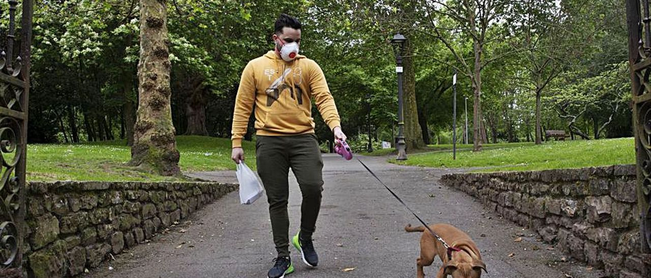 Un hombre y su perro salen del parque de Ferrera.   Ricardo Solís