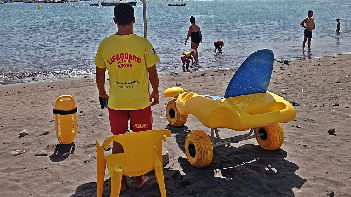 Un socorrista encargado del servicio de baño para personas con movilidad reducida en la playa de Las Galletas.