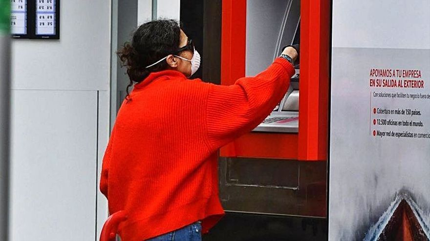 Una mujer retira dinero de un cajero automático. |   // G. SANTOS