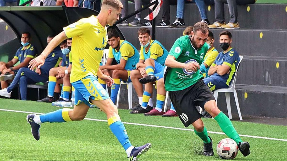 Vianney, del Atlético Paso, intenta superar al amarillo Isidro en el choque disputado en el feudo del conjunto palmero. | | ÓSCAR SIMÓN