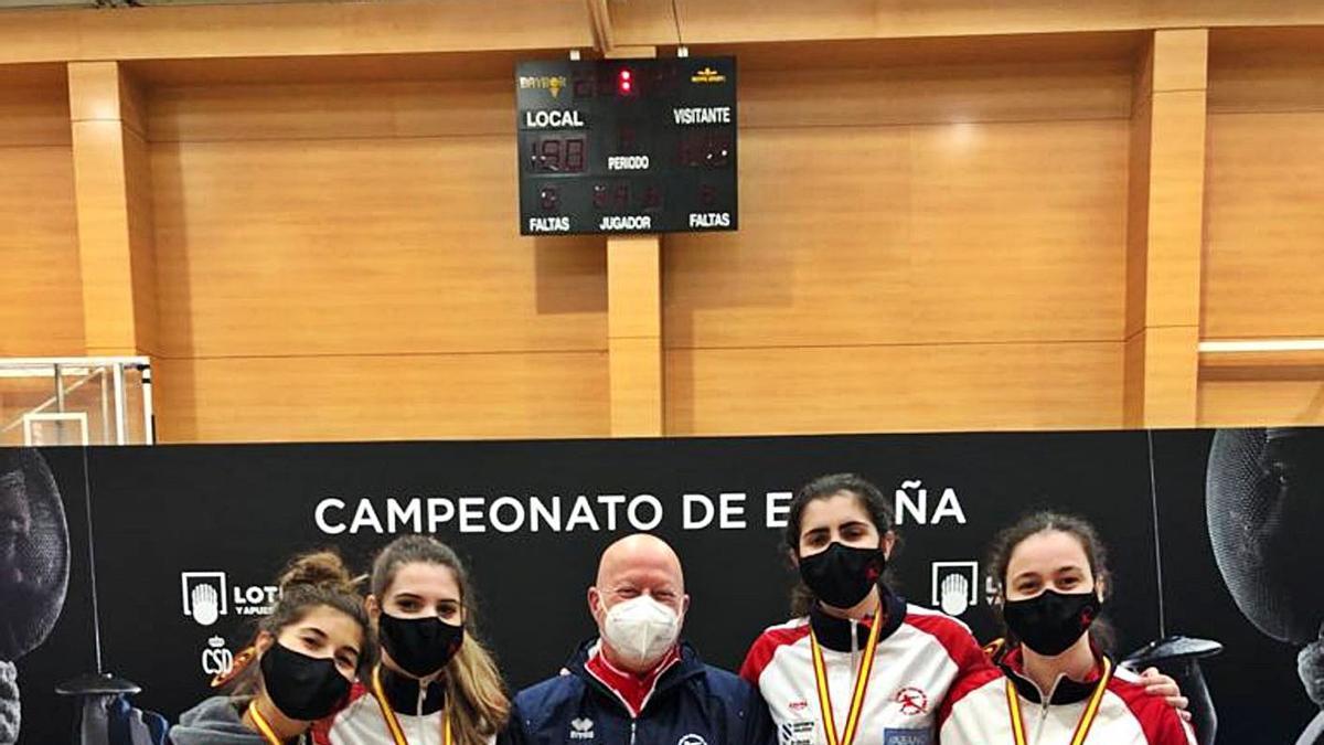 María Mariño (izqda.) con sus compañeras de equipo y con su entrenador Manuel Mariño.    // FDV
