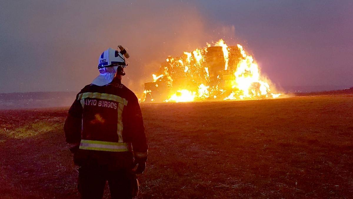 Un bombero frente a las pacas de paja quemándose.