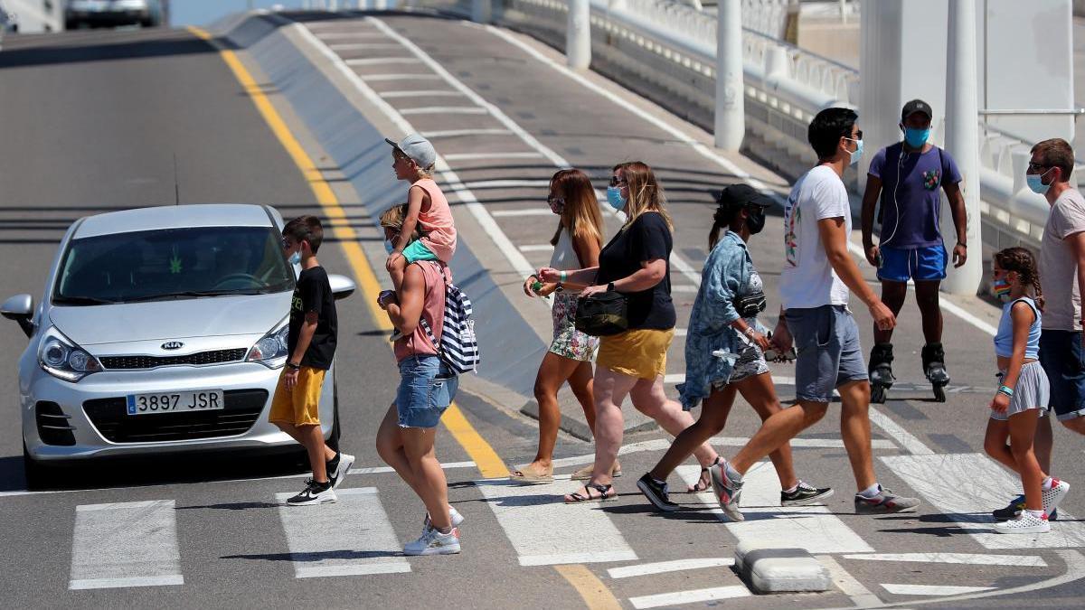 Un grupo de peatones cruza el puente de l'Assut de l'Or.