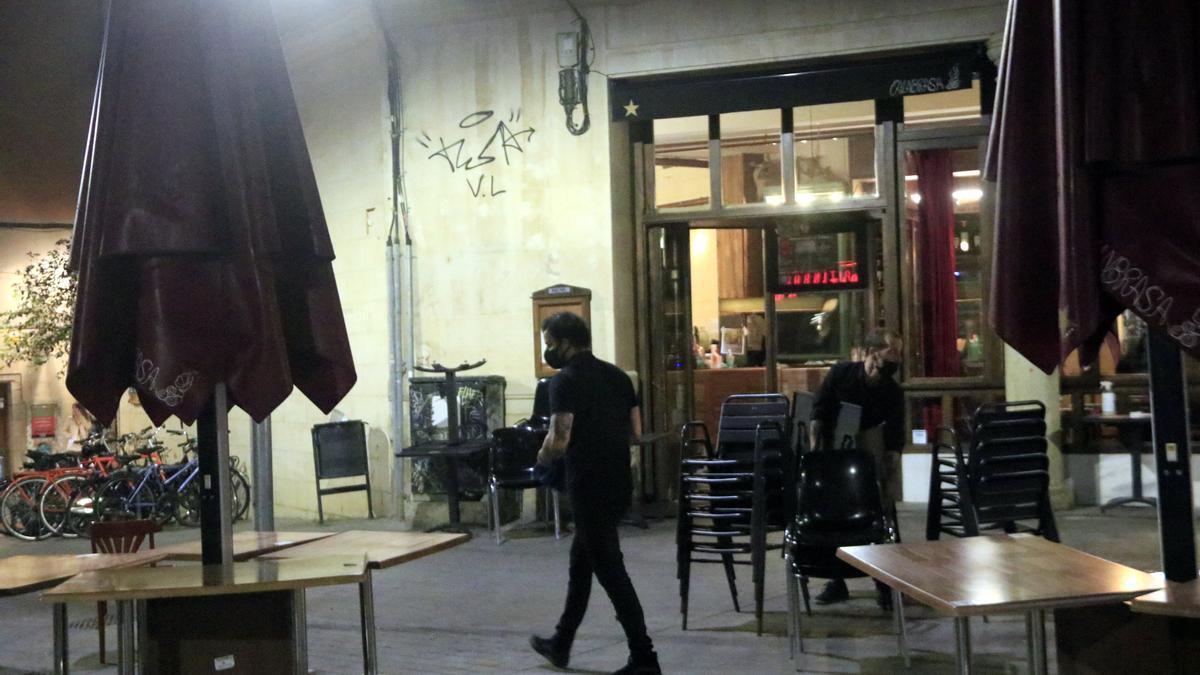 Treballadors d'un restaurant del passeig del Born recollint les taules i cadires a la mitjanit