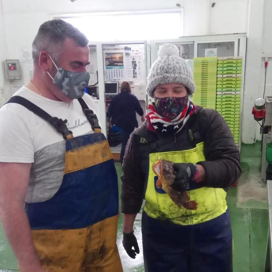 Eladio Costa y una compañera muestran la captura en la lonja de Cambados