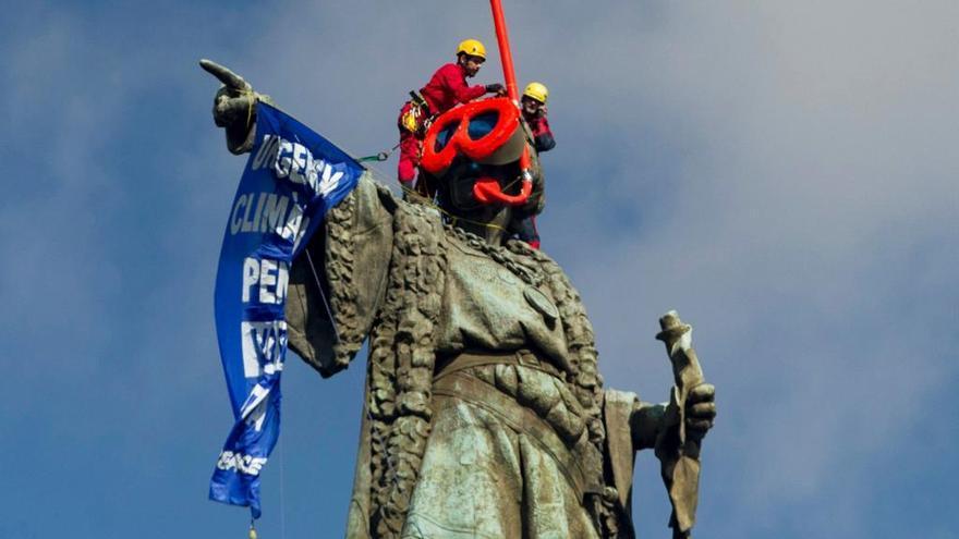 Activistes de Greenpeace col·loquen ulleres de bus a l'estàtua de Colom a Barcelona
