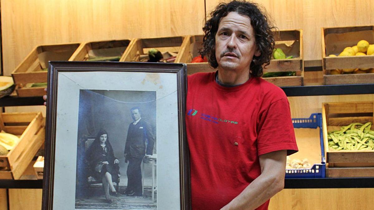 Marc Tibau, dins de la botiga, mostra una fotografia dels seus avis
