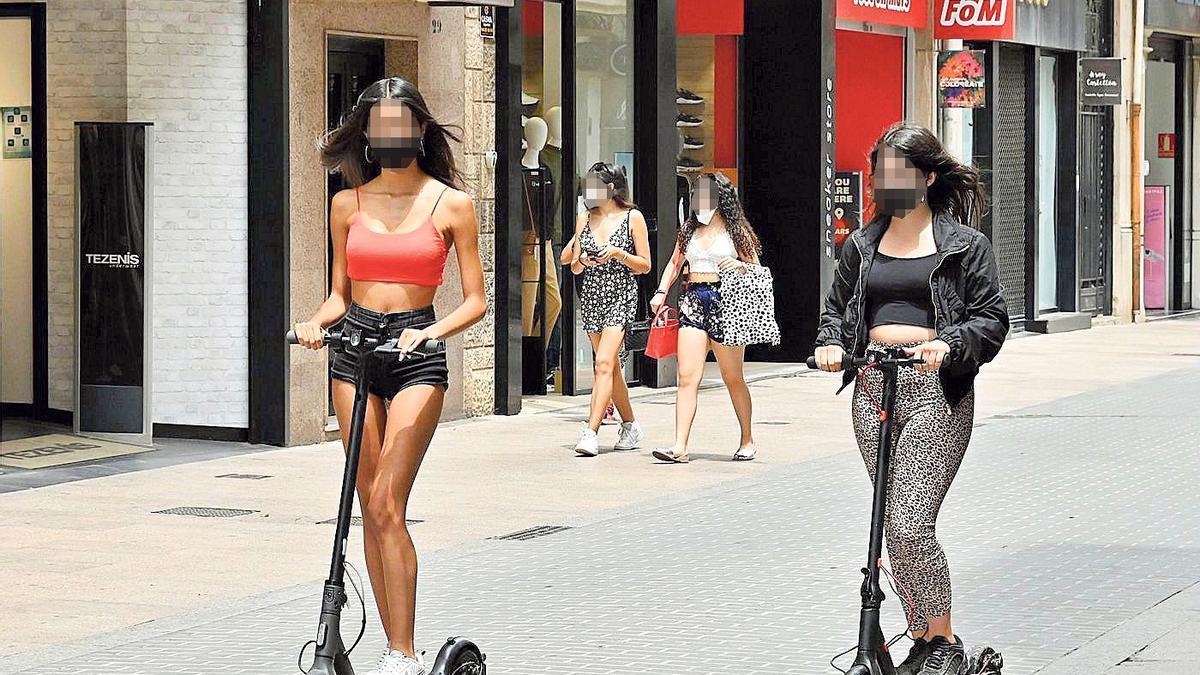 Dos jóvenes con patinete eléctrico por el centro de Castelló