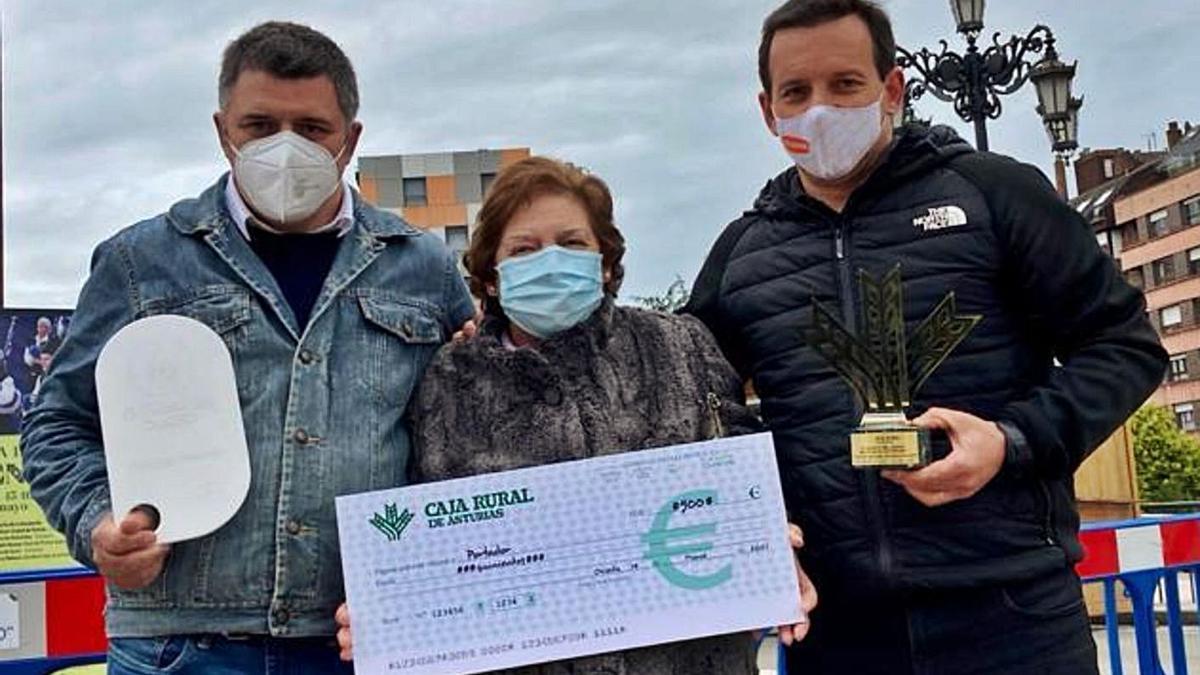 María Aurina Corripio, matriarca de Los Caserinos, con sus hijos Rubén –a la izquierda– y Alberto Amandi, tras recibir el premio en la Feria de la Ascensión, en Oviedo. | V. Alonso