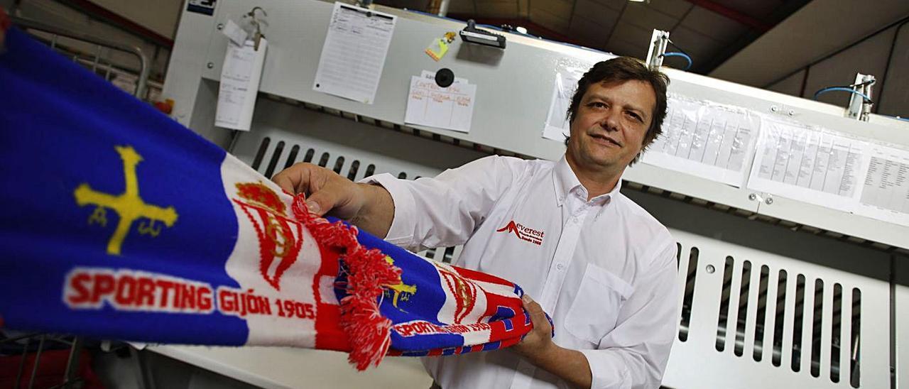 Rogelio Lamar, con una bufanda del Sporting, en la empresa de lavandería industrial en la que trabaja. | Á. González