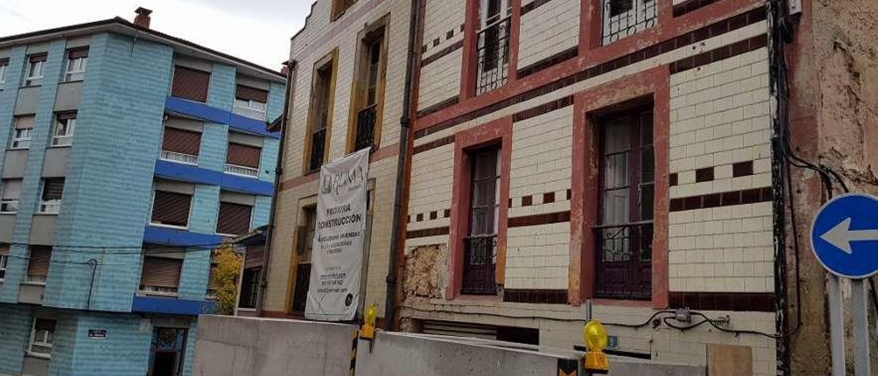 Cartel en un edificio que anuncia la próxima construcción de viviendas en el centro de Candás.