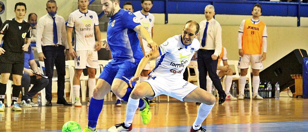 Gabri pugna por un balón ante la atenta mirada del banquillo del Alzira FS. | RAÜL AMAT