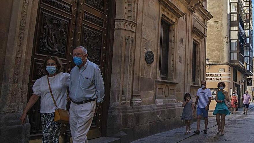 Varios turistas pasean, en verano, por la calle Ramos Carrión