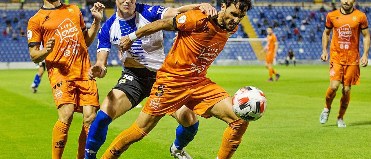 Martínez, del Atzeneta, defiende el balón ante la presión de un rival del Hércules. | ALEX DOMÍNGUEZ/ INFORMACIÓN