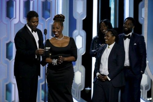 Denzel Washington and his family are seen on stage after Washington won the Cecil B. Demille Award at the 73rd Golden Globe Awards in Beverly Hills