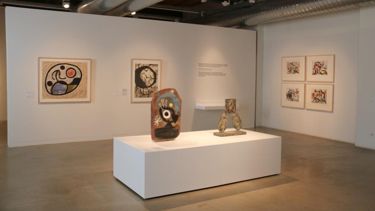 Pla general d'una escultura de Joan Miró amb uns quadres de l'artista de fons