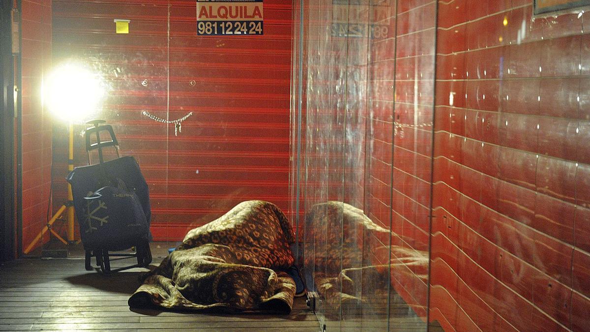 Una persona sin hogar duerme en el portal de un comercio vacío.   | // VÍCTOR ECHAVE