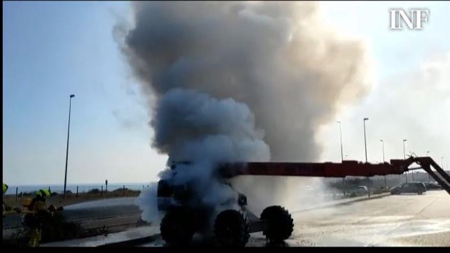 Los bomberos extinguen el incendio de una máquina elevadora cuyo motor ha comenzado a arder con dos operarios arriba