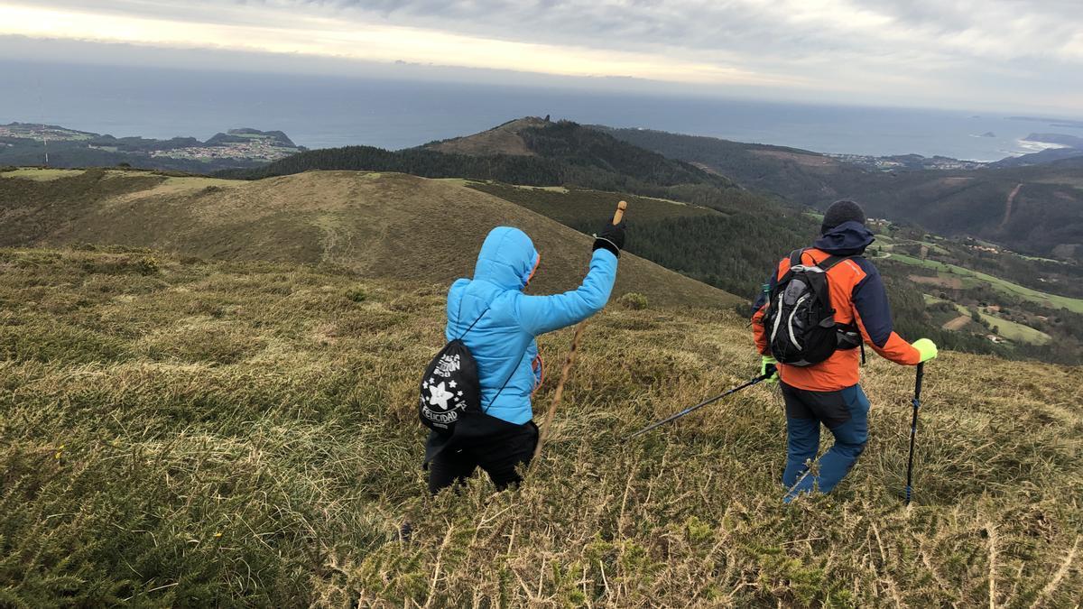 Montañeros descendiendo, contra el viento, de la cima del Lin de Cubel, el pico más alto de Pravia; al fondo, el Cantábrico.