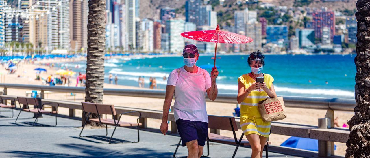 Dos turistas se protegen del sol