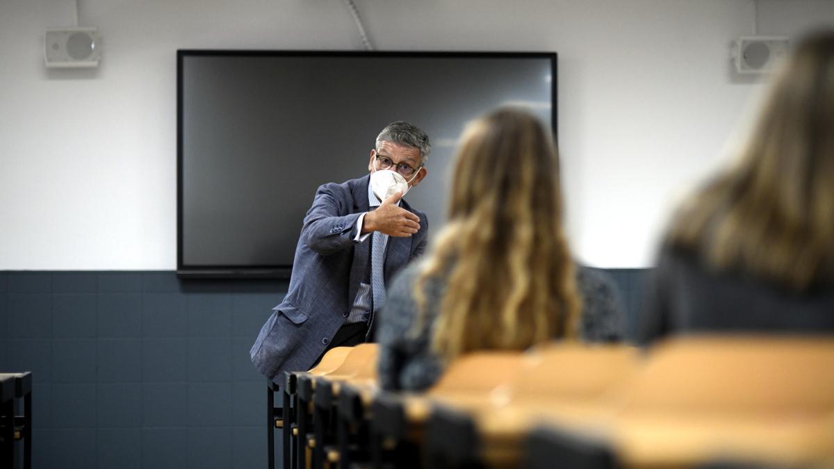 Un profesor da clase con mascarilla.