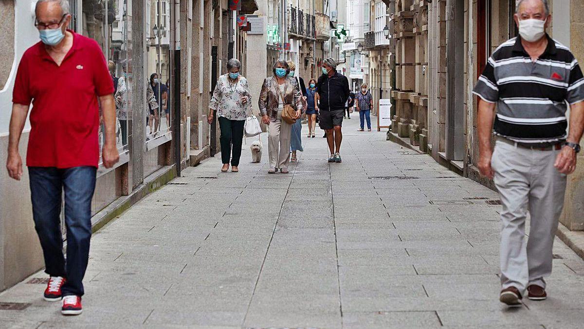 Ciudadanos con mascarillas, ayer, en una calle de Viveiro.