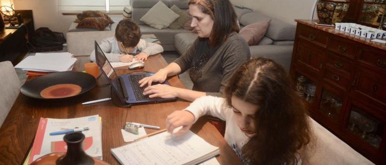 Una mujer teletrabaja mientras sus hijos hacen los deberes.