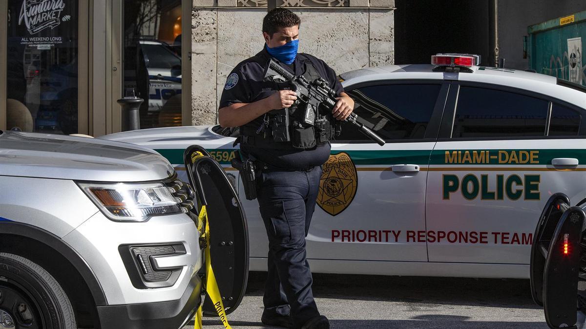Un oficial de policía vigila las afueras de un centro comercial de EEUU después de un tiroteo.