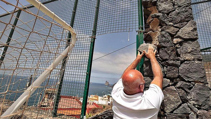 Aldo 'El Tanque de Almáciga' muestra una de las piedras del muro de cerramiento que está a punto de caer. | | MARÍA PISACA