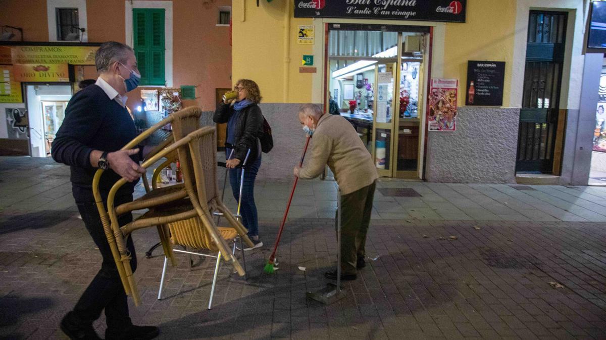 Los trabajadores del bar España de la calle Oms retiran el mobiliario de terraza el martes poco antes de las seis de la tarde, el día que entró en vigor el nuevo horario de cierre obligatorio