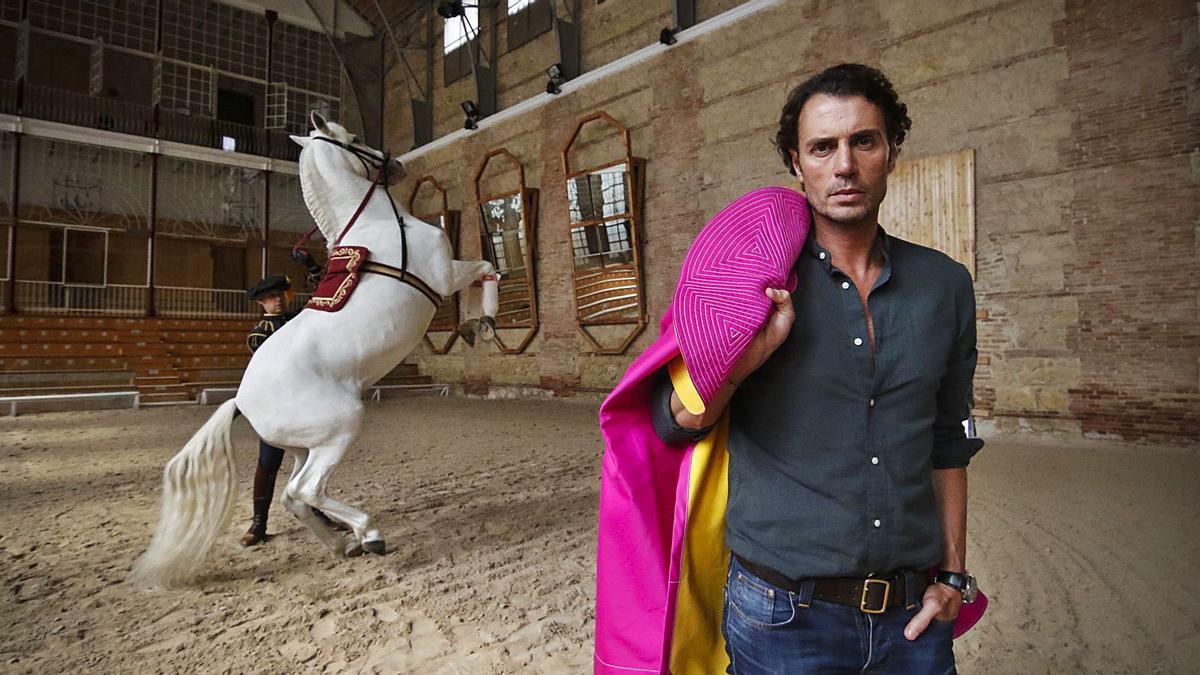 Finito de Córdoba, con un capote al hombro, en Caballerizas Reales. Al fondo, un caballo en una elevada.