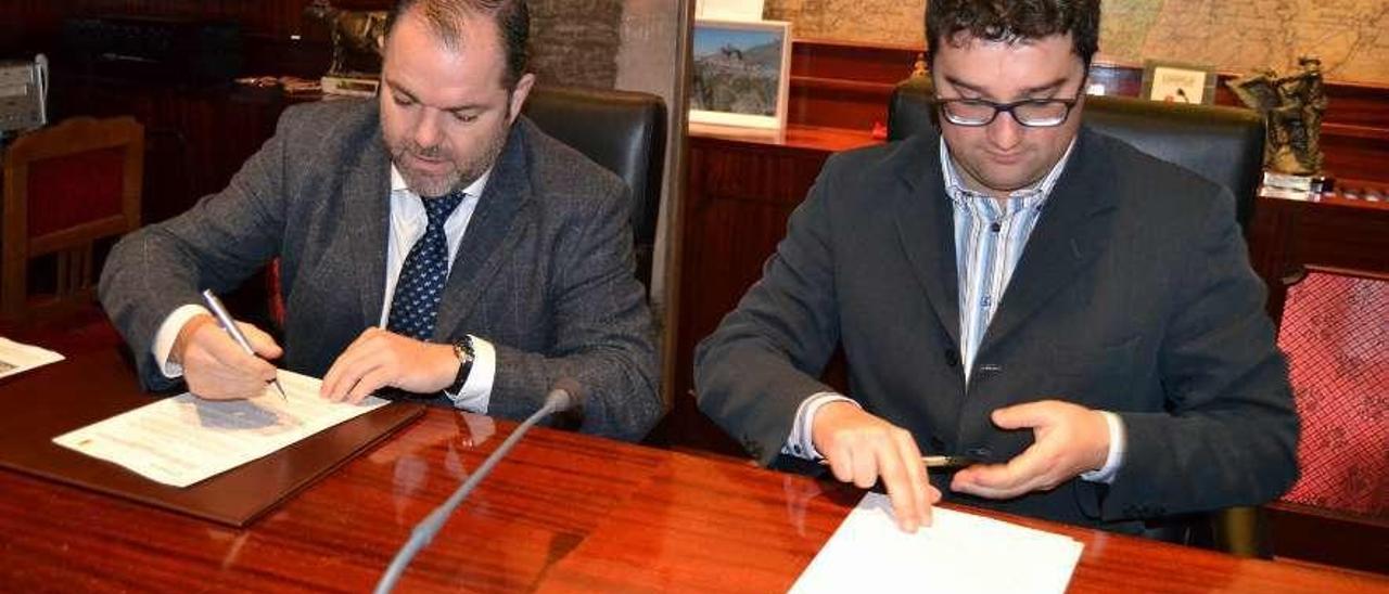 El presidente de la Cámara de Comercio de Oviedo, Carlos Paniceres, y el alcalde de Valdés, Óscar Pérez, durante la firma del convenio, ayer.