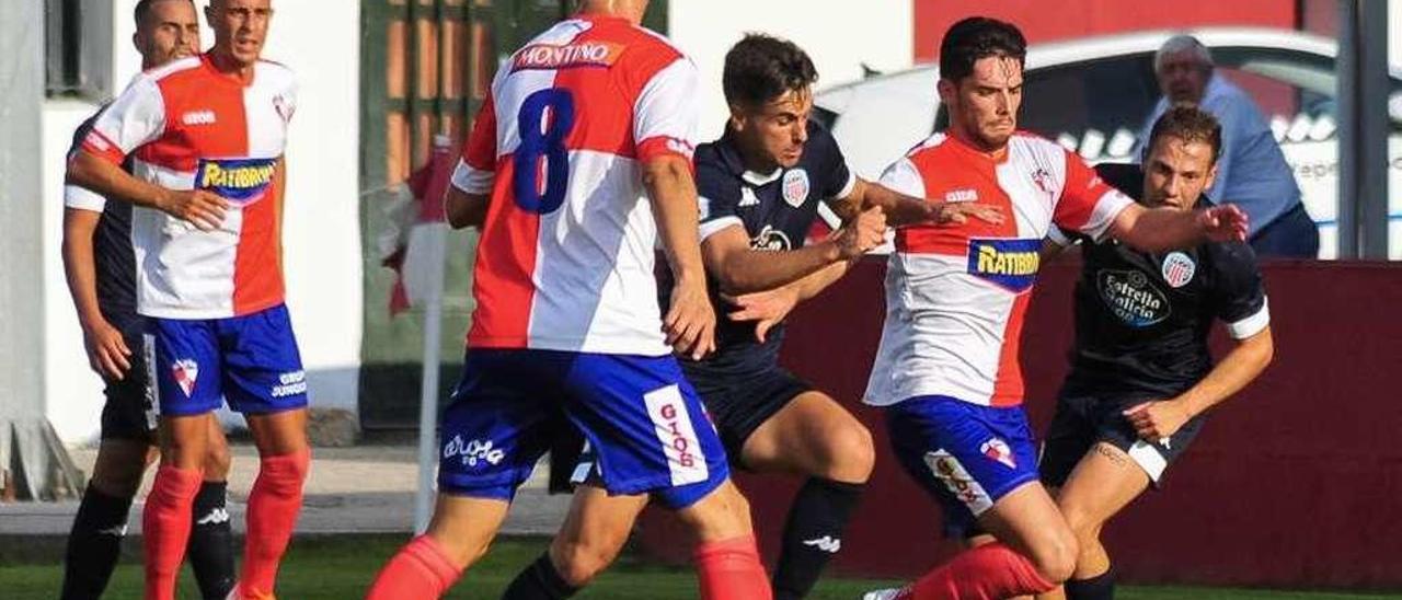 Un jugador del Arosa intenta escapar de un rival, durante la primera jornada de liga. // Abella