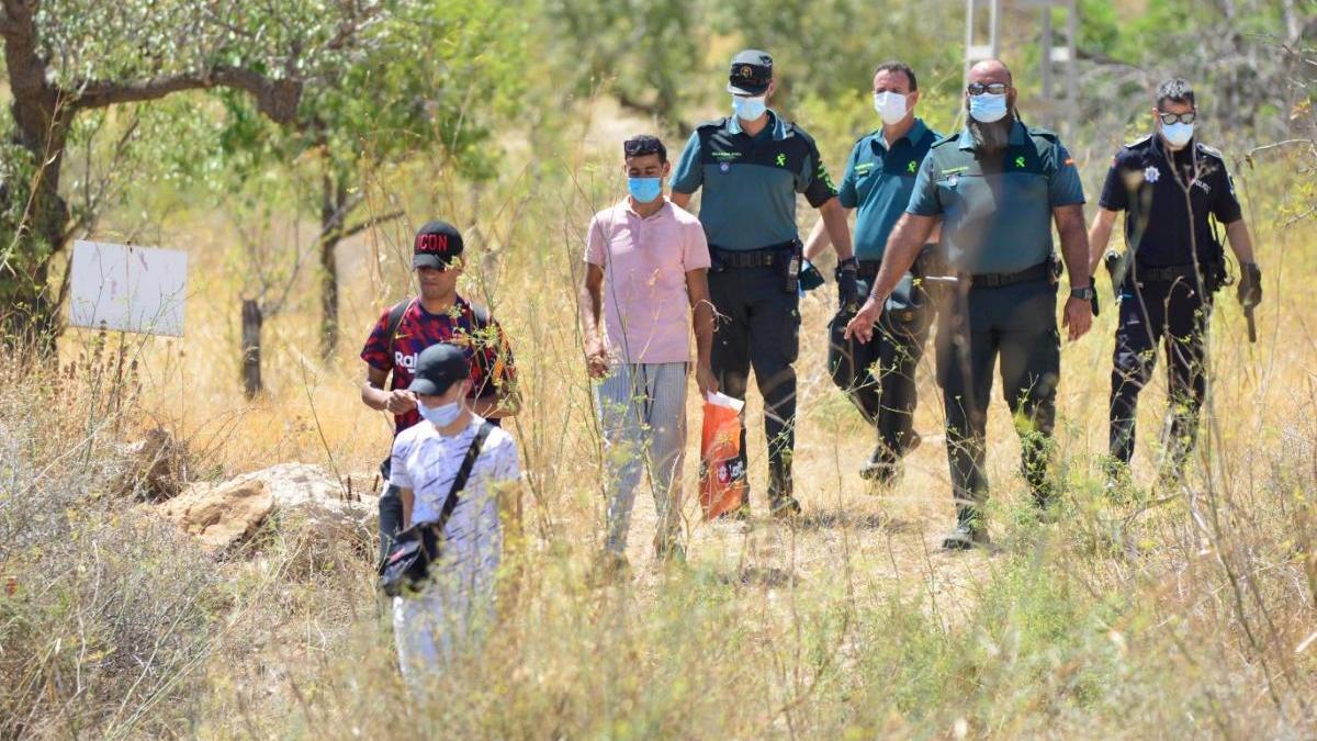 Agentes bajan del monte con migrantes localizados.