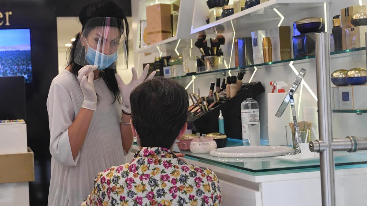 Una dependienta de una tienda de cosmética atiende con sistemas de protección en Bolonia.