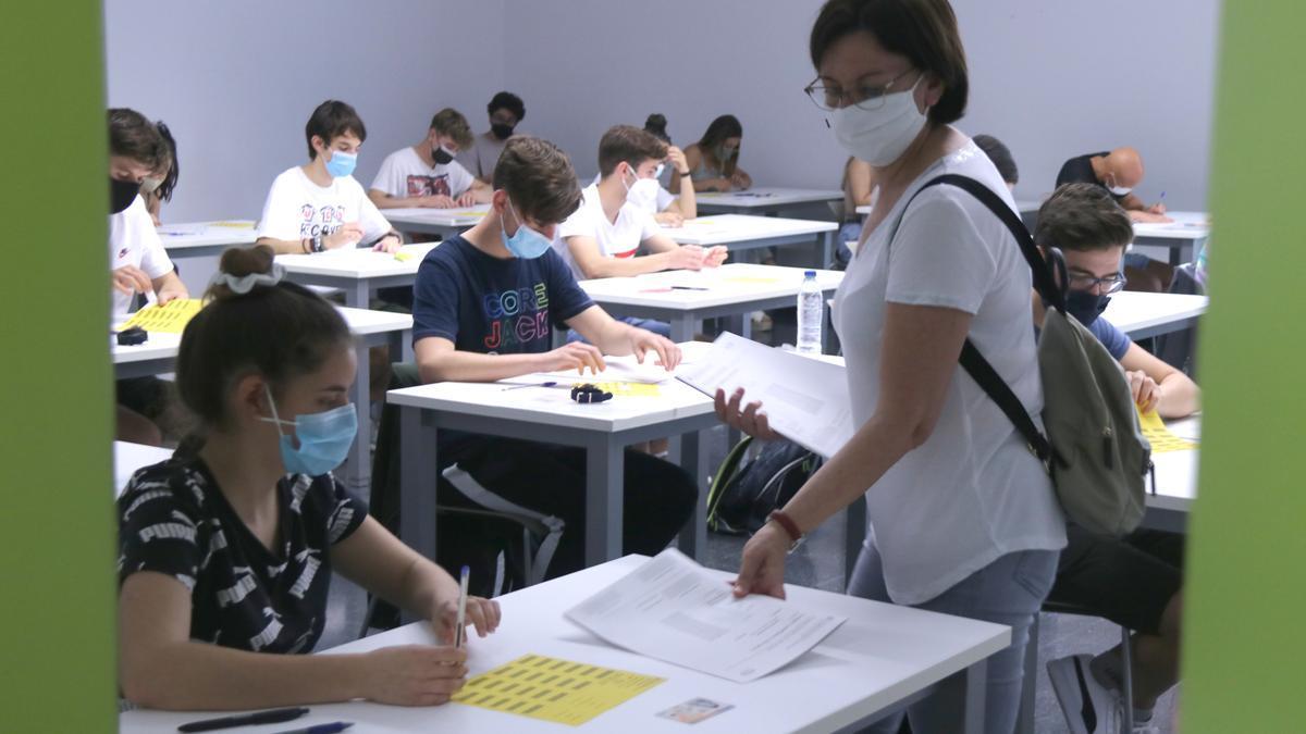 Una professora repartint exàmens en una aula en el primer examen de selectivitat