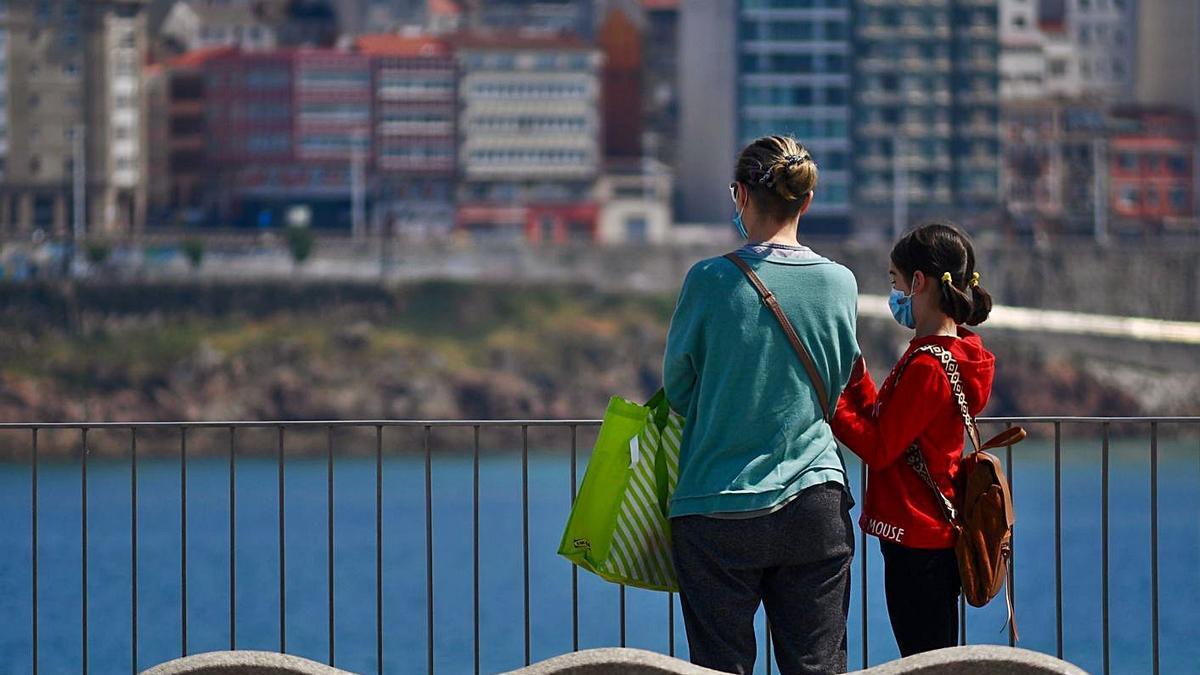 Una mujer y una niña observan el mar en el Paseo Marítimo de A Coruña.     // CARLOS PARDELLAS