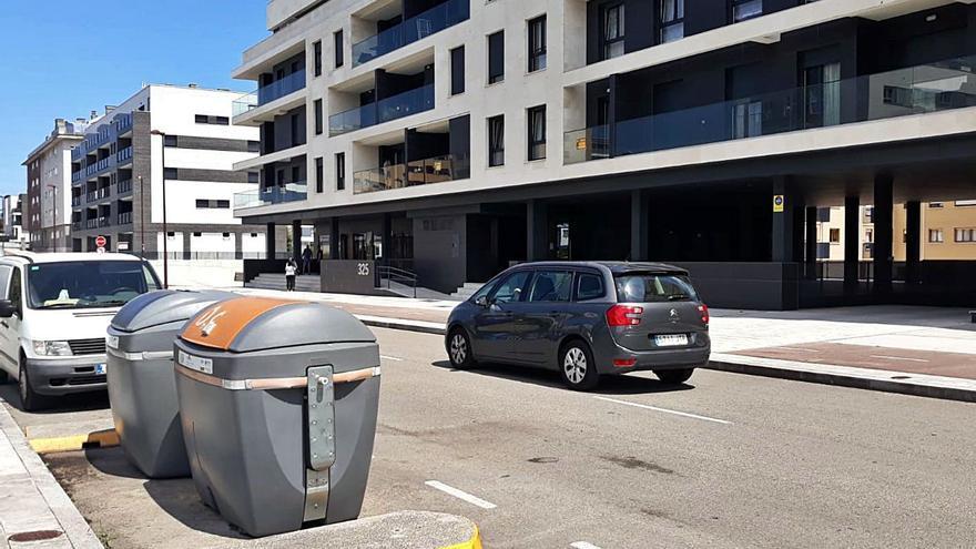 Contenedor de basura en la calle Genaro Suárez Prendes, en Nuevo Roces, donde apareció el cadáver del bebé, justo delante del edificio donde vivía la pareja. En el recuadro, Silvia A. M., la madre del bebé.