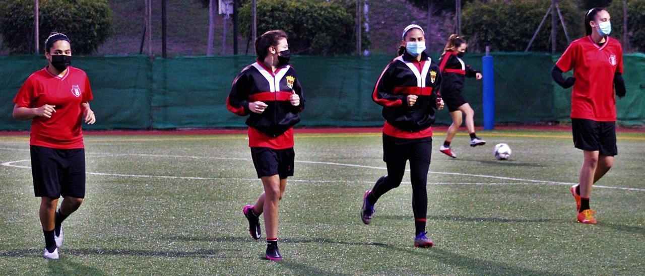 Primer plano de cuatro futbolistas del Unión Viera Femenino C, durante el entrenamiento de ayer, con mascarilla, en el césped artificial del Alfonso Silva.   | | UNIÓN VIERA