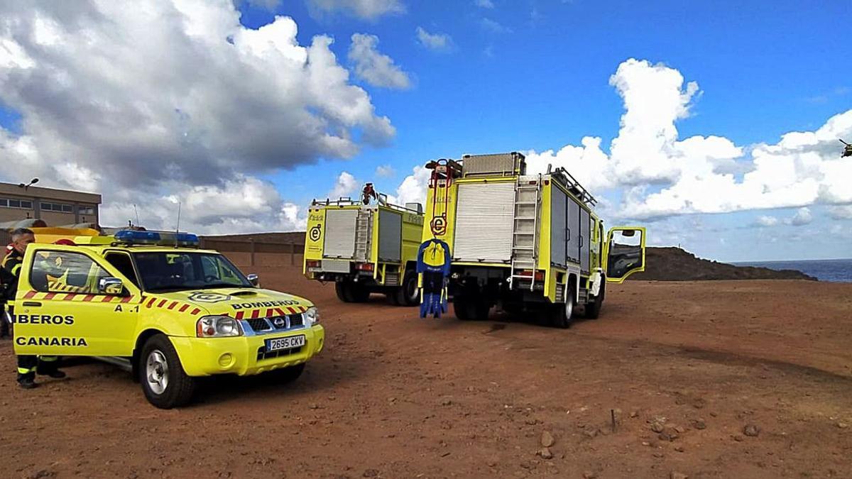 Los bomberos en la zona de Roque Prieto, ayer, junto a las desaladoras de Guía, mientras un helicóptero sobrevuela la zona.